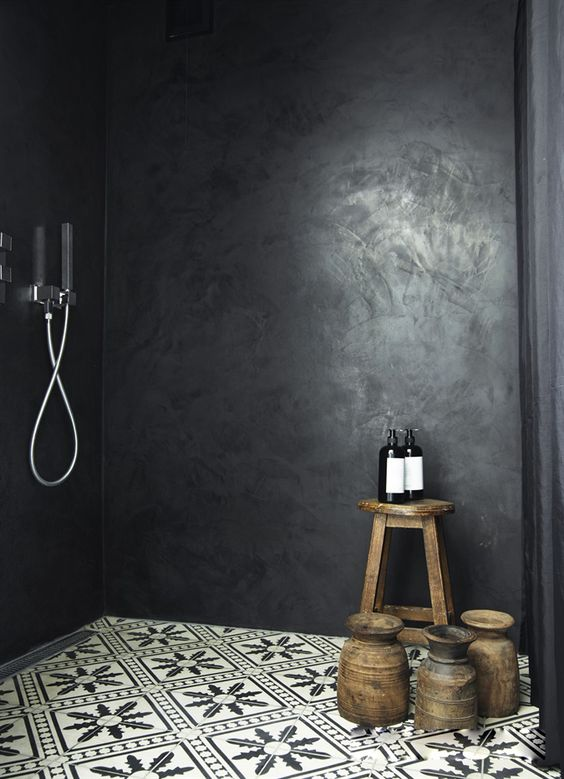 black stone in the shower and mosaic tiles on the floor make the space eye-catching and moody, which is trendy