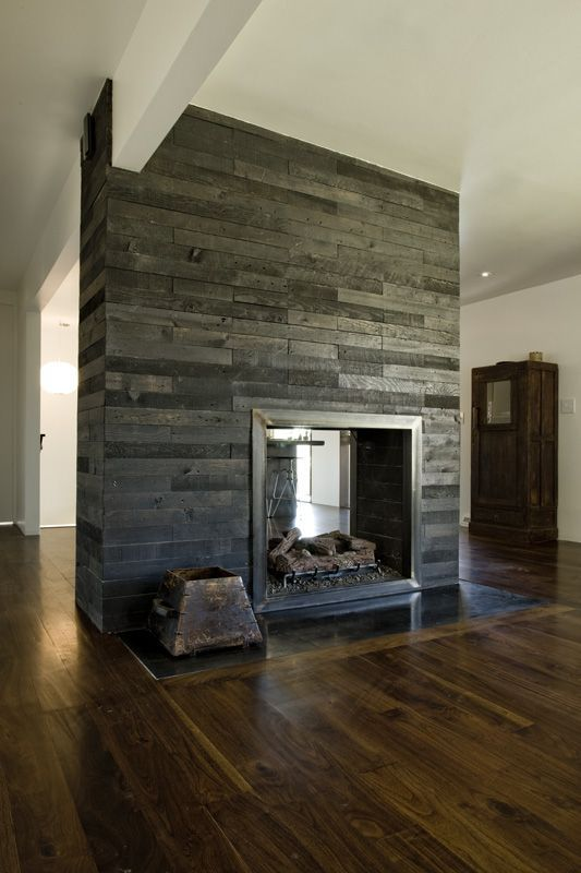 a double-sided fireplace clad with reclaimed grey and black wood brings texture and a cool look to the space