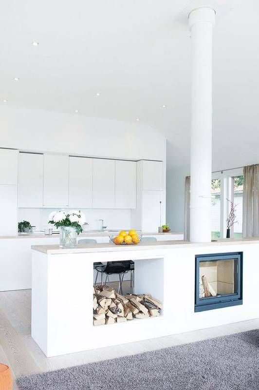a minimalist white kitchen is made more interesting with a kitchen island with an integrated hearth and firewood storage
