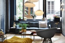 19 a modern space with black walls and furniture, colorful touches and pendant lamps, the space is filled with light and doesn't seem gloomy