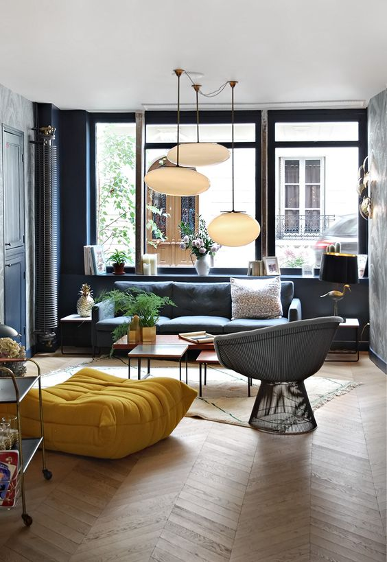 a modern space with black walls and furniture, colorful touches and pendant lamps, the space is filled with light and doesn't seem gloomy