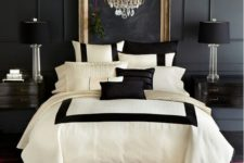 19 an elegant space with a black panel wall, black lamps and nightstands and a glam chandelier