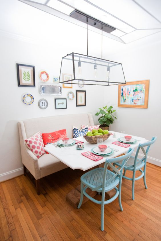 a colorful eclectic dining space with a comfy bench and blue chairs