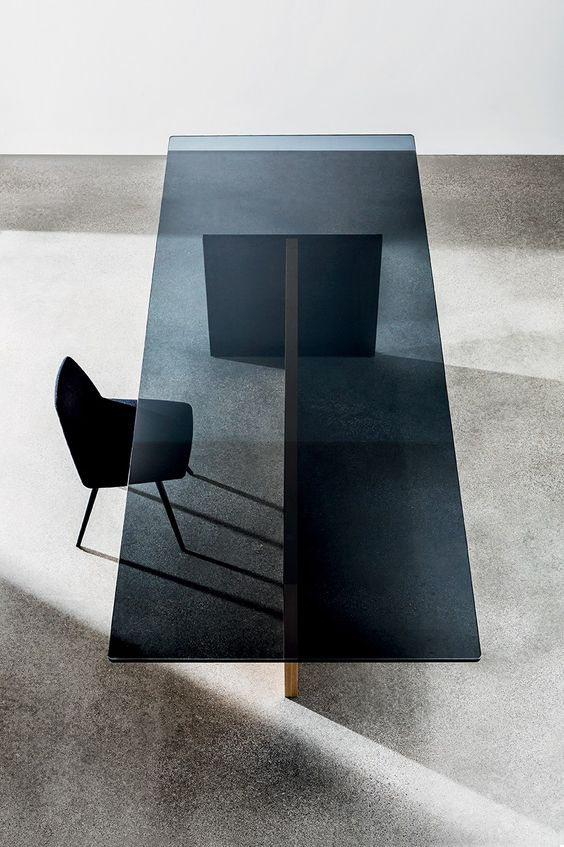 a dining table with wood sheet legs and a smoked glass tabletop will surprise your guests