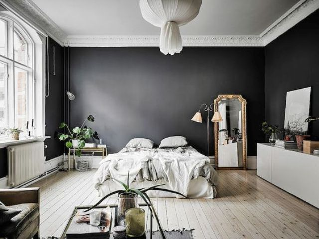 a dramatic Scandinavian space with black walls looks airy thanks to lots of light and light-colored wooden floors
