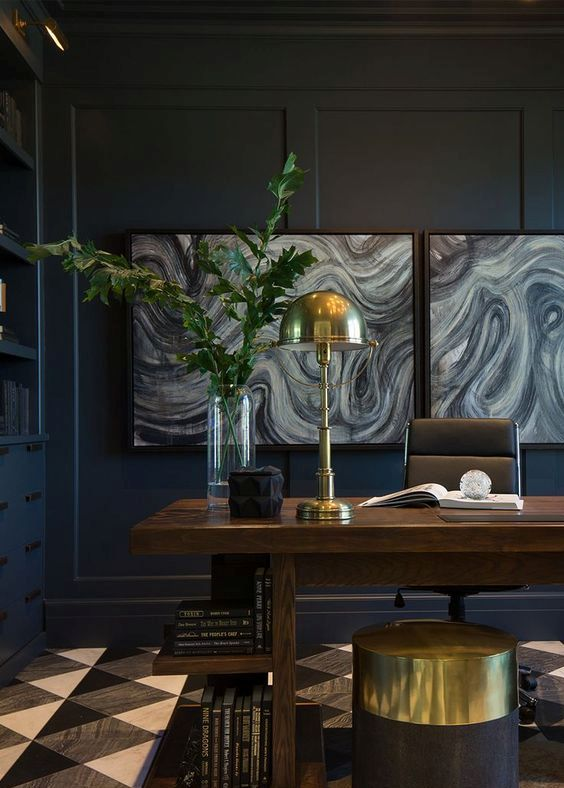 a luxurious home office with black walls, interesting artworks and brass touches for a chic look