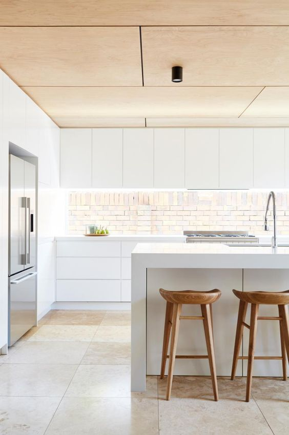 a minimalist white kitchen with a wooden ceiling, stools and an eye-catchy backsplash