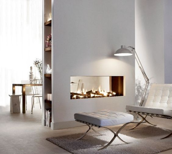 a modern white space with a double-sided glass fireplace for the kitchen and living room