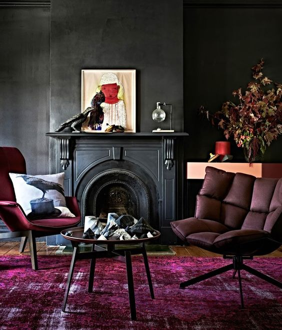 a moody space with black walls, a fuchsia rug and furniture and artworks