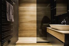 20 black walls and light-colored wooden wall and floor plus a smoked glass shower wall create a chic modern look