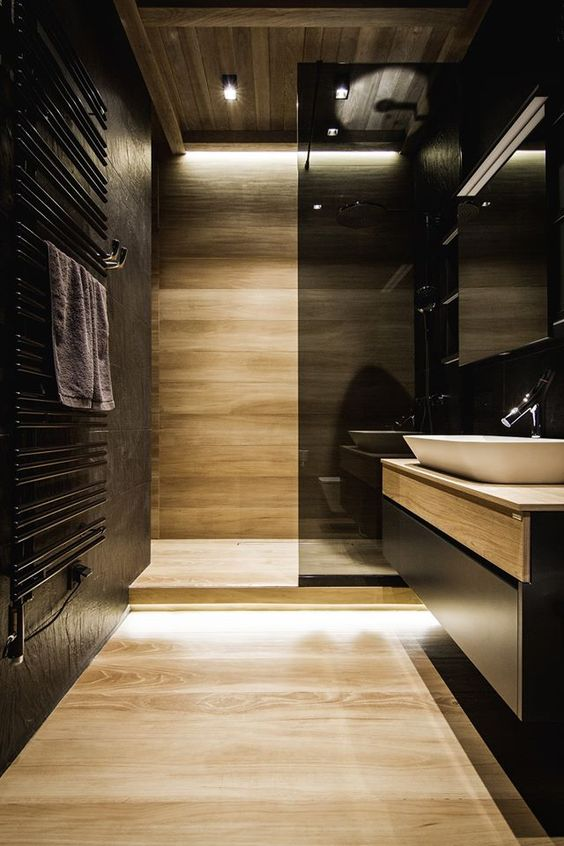 black walls and light-colored wooden wall and floor plus a smoked glass shower wall create a chic modern look