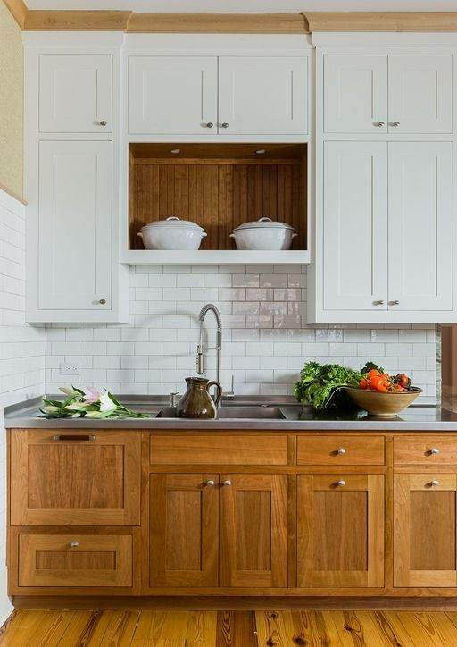 a cozy rustic kitchen with white and wooden cabinets of traditional design and a subway tile backsplash