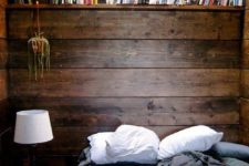 21 a cozy small rustic bedroom with a stained wooden wall and a matching bookshelf over the bed