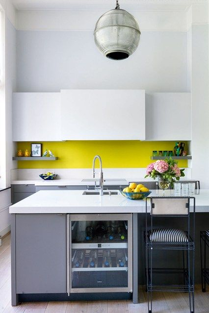 a minimalist kitchen in grey and white and with a neon yellow backsplash for a colorful touch