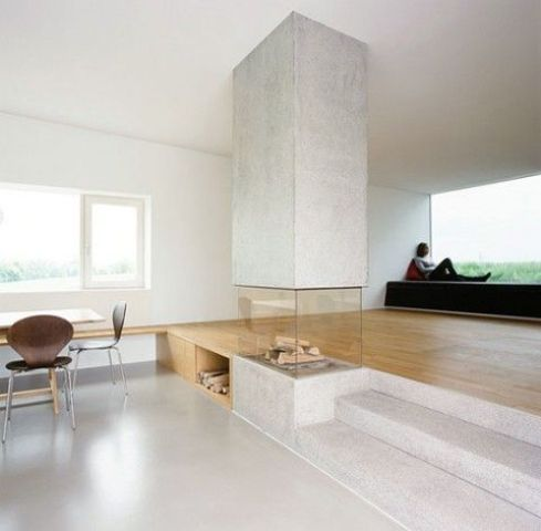 a modern concrete fireplace is a feature of a living and dining space