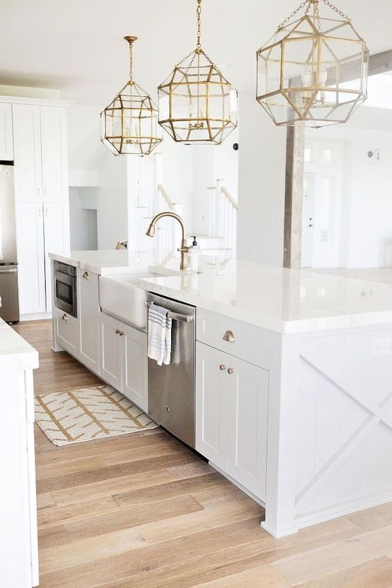 a modern farmhouse kitchen with brass lamps and details and stainless steel appliances