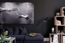 21 a moody space with black walls, a photo artwork, black furniture and a cool rug