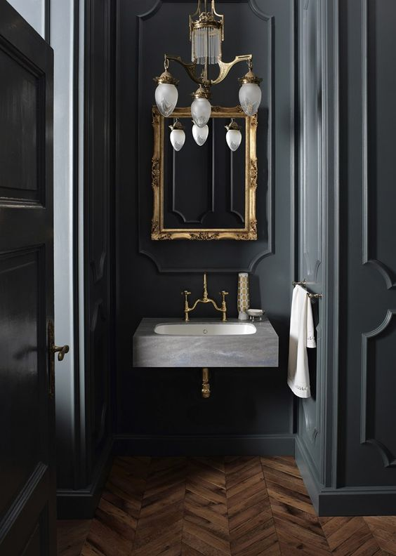 a vintage chandelier, a mirror in a vitnage gold frame and brass fixtures make a cool 1920s moody space