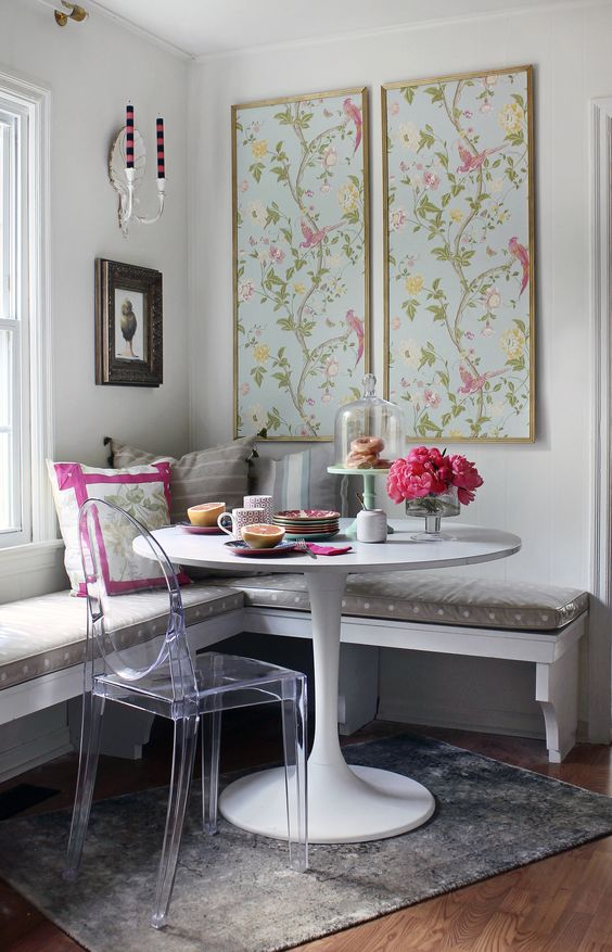 a wall-mounted corner bench with a cushion on top, an acrylic chair and floral artworks for a cheery breakfast nook