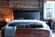 22 a cabin-inspired bedroom with a dark stained wooden wall, a leather bed and a rug that imitates wood slices