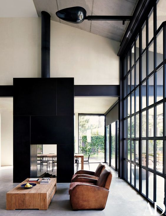 a large double sided fireplace clad with black tiles steals the show and catches every eye