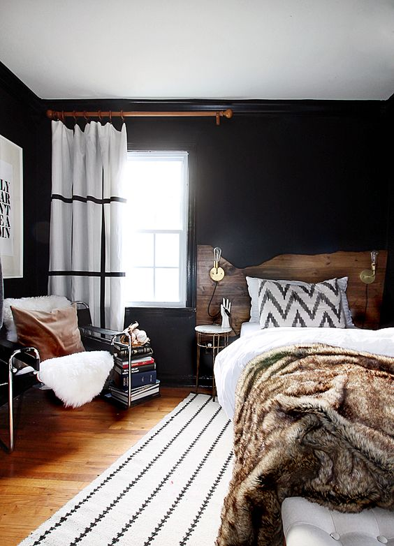 a mid-century modern space with a boho feel, black walls are balanced with whites and natural wood