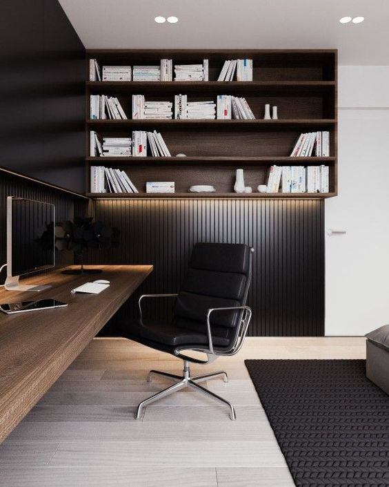 a modern masculine space with black wood panel walls and a lit up wall shelving unit, a wall-mounted desk