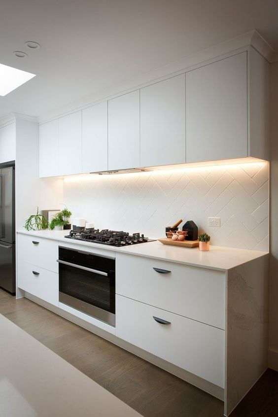 a modern white kitchen is made more eye-catchy with lights and a geometrically clad backsplash