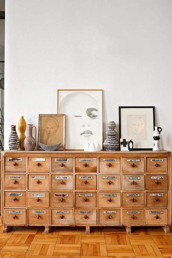 a vintage apothecary cabinet of light-colored wood to make a statement in a living room