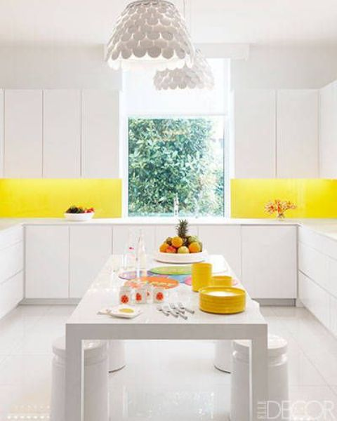 an all-white kitchen with a bold yellow backsplash to add a colorful touch and raise your mood