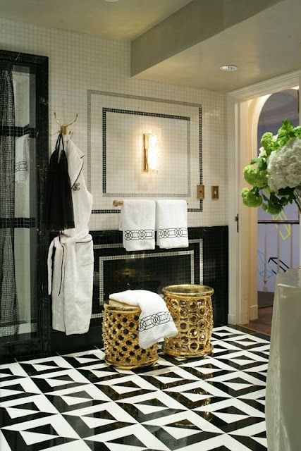 gold geometric stools and brass fixtures and details thoughout the bathroom add a glam feel