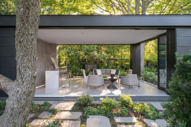 sliding glass doors completely open the living room to outdoors making it an outdoor salon