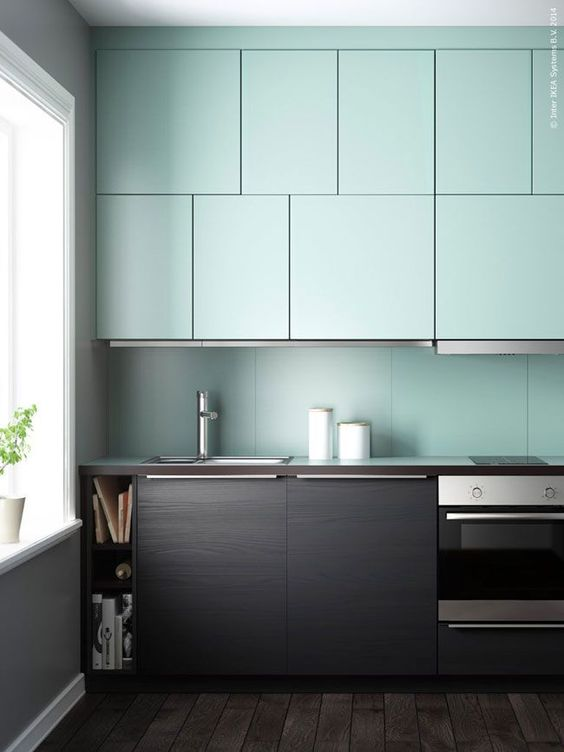 a dark stained wood and mint kitchen with a mint backsplash looks very contrasting and unusual