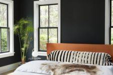 23 a modern bedroom with black walls, a leather upholstered bed and cool lamp cluster looks relaxing and very chic