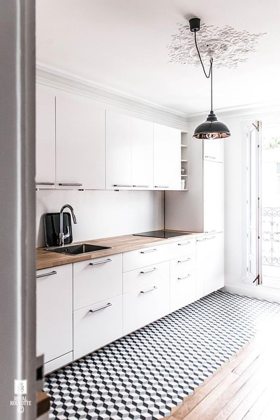 a modern white kitchen with a geometric floor and a wooden countertop to make it look more interesting