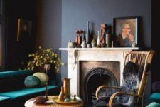 23 a refined dark living room with black walls, amarald upholstered furniture, a vintage fireplace and some beautiful vases