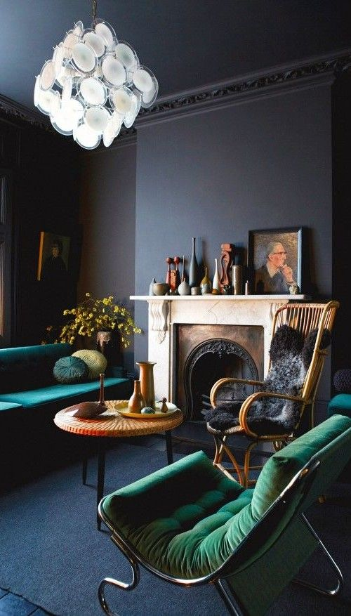 a refined dark living room with black walls, amarald upholstered furniture, a vintage fireplace and some beautiful vases