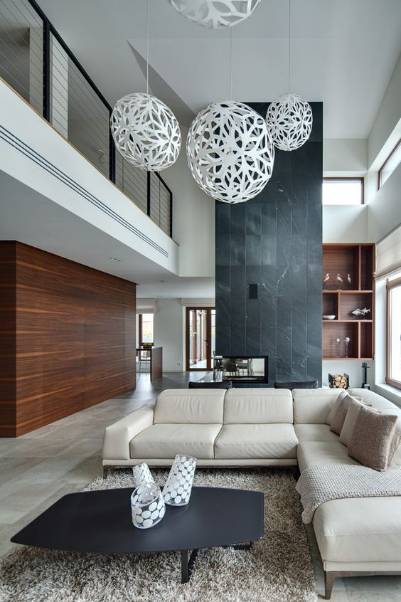 a saturated wooden wall and a black stone fireplace wall define this modern space