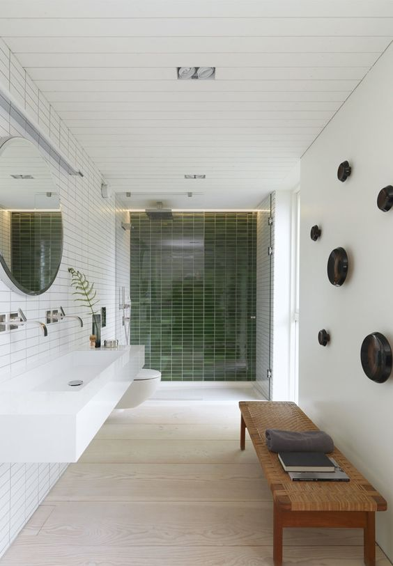 a stylish wicker bench and green tiles in the shower creat a natural ambience in the bathroom