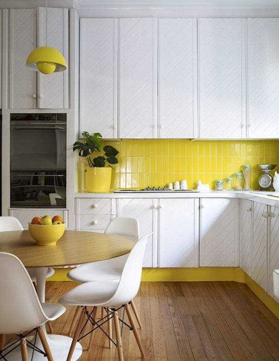 a white kitchen is enlivened with a neon yellow tile backsplash, lamps and a planter