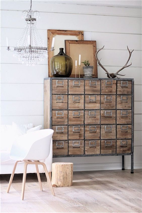 an apothecary cabinet with metal framing adds an industrial and vintage touch to the space