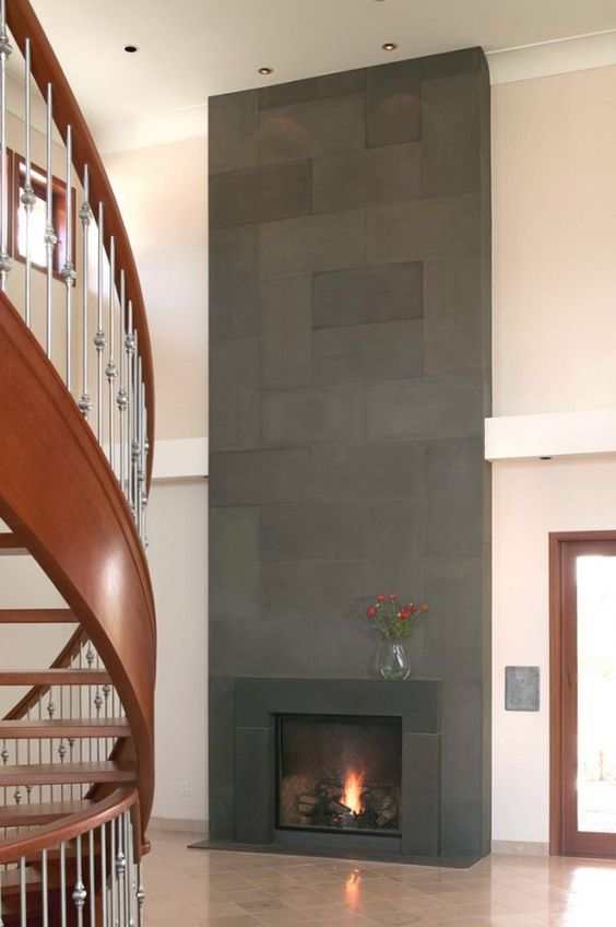 a modern fireplace clad with dark tiles and metal that matches looks very bold in a neutral space