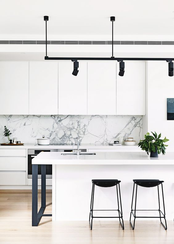 a modern white kitchen with a marble backsplash, black stools, lamps and legs