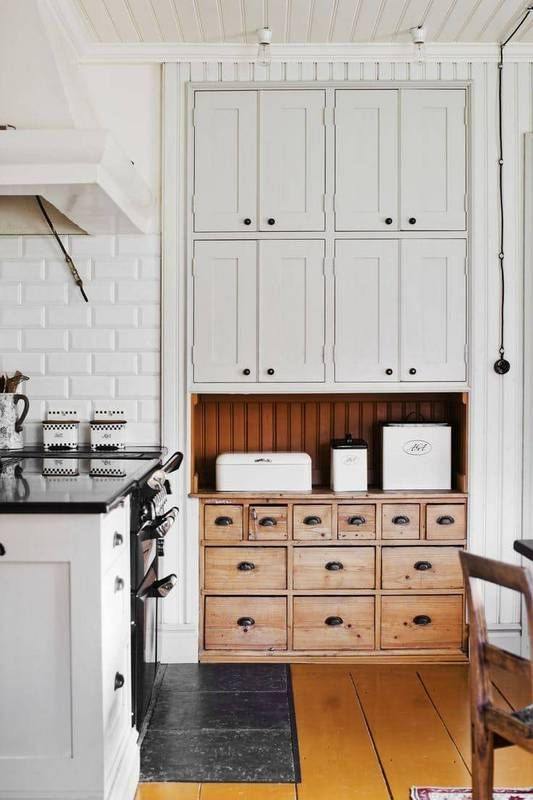 a wooden apothecary cabinet can stand out in a neutral kitchen