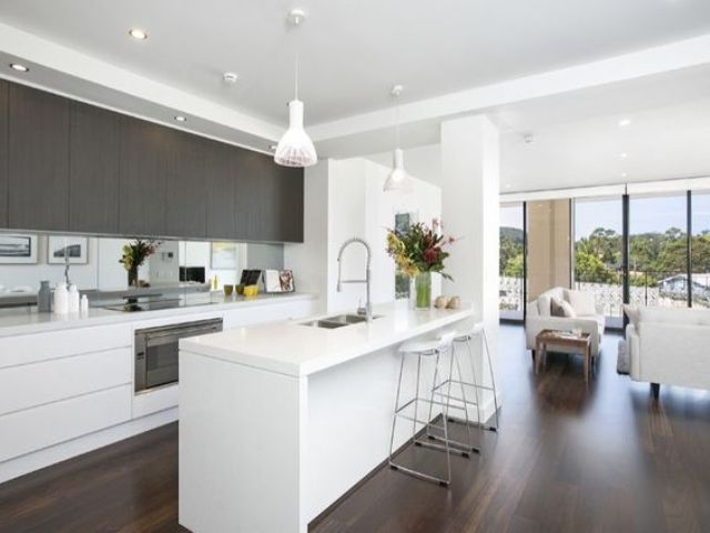 a minimalist space with white and dark stained wooden cabinets and a white kitchen island looks sleek and chic