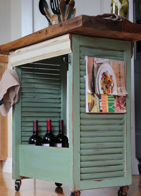 a mobile kitchen island made from shutters, painted mint and with a wooden countertop