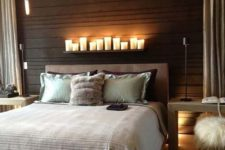 25 a modern bedroom with a headboard wall clad with dark wood and a shelf with candles to highlight it