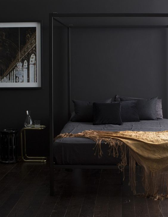 a moody bedroom with a framed black bed, black walls, bedding and some gold and brass touches here and there