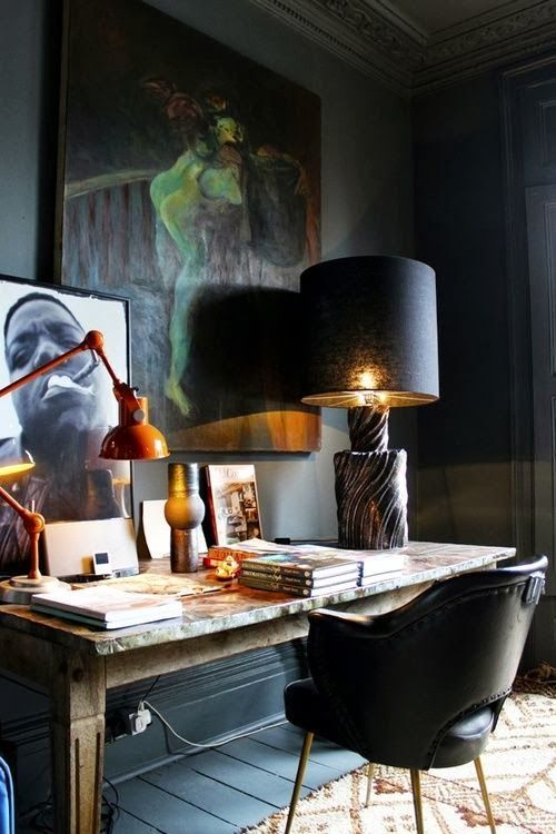 a refined home office with black walls, floor and furniture and gorgeous artworks for an art lover