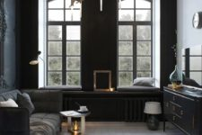 25 a small refined living room with two black walls, a black sofa and sideboard, modern lamps and lots of lght